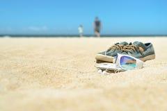 Sonnenbrille und Schuhe auf dem Strand mit Leuten auf Hintergrund Lizenzfreie Stockfotos