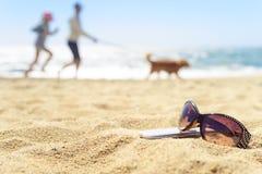 Sonnenbrille und Telefon auf dem Strand mit Leuten auf Hintergrund Stockfotos