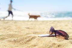 Sonnenbrille und Telefon auf dem Strand mit Leuten auf Hintergrund Lizenzfreies Stockfoto