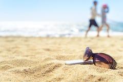 Sonnenbrille und Telefon auf dem Strand mit Leuten auf Hintergrund Lizenzfreies Stockbild