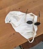Sonnenbrille und weiße Tasche im Holztisch stockfotografie