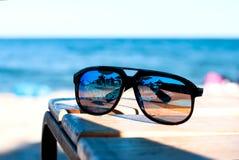 Sonnenbrillelüge auf einem Strand auf Sand Lizenzfreies Stockbild