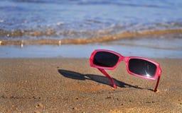 Sonnenbrillen auf dem Sand Stockfotos