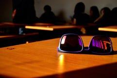 Sonnenbrillen auf dem Schreibtisch des Studentensommers Stockfotografie