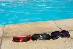 Sonnenbrillen auf Poolrand Stockbild