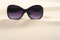 Sonnenbrillen auf Sand Stockfoto