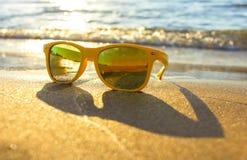 Sonnenbrillen auf Strand nahe dem Meer Gelbe Sonnenbrille auf dem Hintergrund von Meer bewegt auf das Ufer von einer Tropeninsel  Lizenzfreies Stockfoto