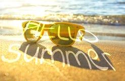 Sonnenbrillen auf Strand nahe dem Meer Gelbe Sonnenbrille auf dem Hintergrund von Meer bewegt auf das Ufer von einer Tropeninsel  Stockbild