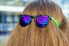 Sonnenbrillen mit Farbgläsern auf dem Nacken des Mädchens Lizenzfreie Stockfotografie