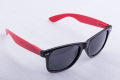Sonnenbrillen mit roten Tempeln auf einer weißen Oberfläche Lizenzfreie Stockbilder