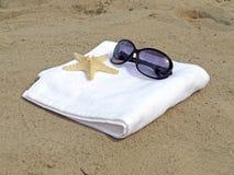Sonnenbrillen und Starfish auf weißem Tuch Lizenzfreies Stockbild