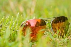 Sonnenbrillenahaufnahme auf einem grünen Rasen stockfoto