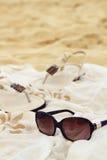 Sonnenbrillesarongsandalen auf dem Strand Lizenzfreies Stockfoto