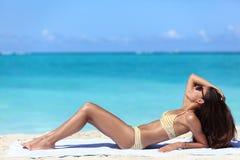 Sonnenbräunefrau, die eine Bikinisonnenbräune auf Strand erhält Stockbilder