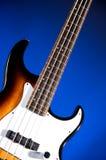 Sonnendurchbruch-Baß-Gitarre getrennt auf Blau lizenzfreie stockfotografie