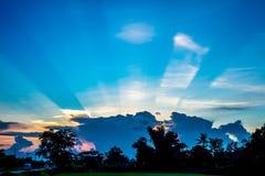 Sonnendurchbruch hinter den Wolken mit Hintergrund des blauen Himmels Stockbild
