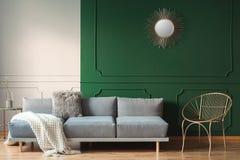 Sonnenform wie Spiegel auf grüner Wand des Wohnzimmerinnenraums mit skandinavischem Sofa mit Kissen lizenzfreies stockbild
