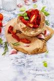 Sonnengetrocknete Tomaten mit Kräutern und Seesalz auf cuting Brett stockbilder