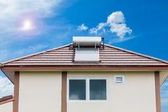 Sonnenkollektor für Heißwassersystem auf Dach auf BAC des blauen Himmels und der Sonne Stockfoto