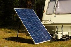 Sonnenkollektor mit altem Wohnwagen in einem Kiefernwald Stockbild