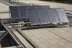 Sonnenkollektoren über einem Gebäudedach Stockbilder