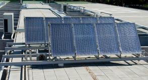Sonnenkollektoren über einem Gebäudedach Lizenzfreies Stockfoto