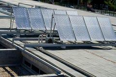 Sonnenkollektoren über einem Gebäudedach Stockfoto