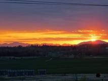 Sonnenkollektoren auf dem Gebiet bei Sonnenuntergang mit Bergen gestalten landschaftlich lizenzfreies stockbild