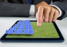 Sonnenkollektoren auf Gras auf Tablette mit der Geschäftsmannhand stockfotografie