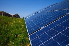 Sonnenkollektoren, blauer Himmel und grünes Gras Stockbild