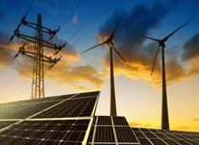 Sonnenkollektoren mit Windkraftanlagen und Strommast bei Sonnenuntergang Stockbild