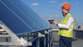 Sonnenkollektoren wird durch einen männlichen Experten in der Arbeitskleidung überprüft stock video