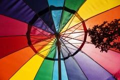 Sonnenlicht, das durch mehrfarbigen Patio-Regenschirm glänzt Lizenzfreies Stockfoto