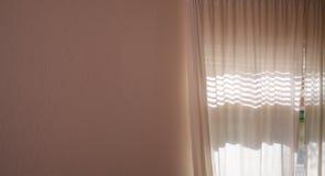 Sonnenlicht, das durch Vorhänge und leere Wand glänzt Lizenzfreie Stockfotografie