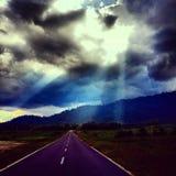 Sonnenlicht, das unten von den starken Wolken im Himmel glänzt Lizenzfreie Stockfotografie