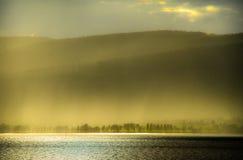 Sonnenlicht durch Regen durch den Fjord Stockbilder