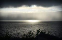 Sonnenlicht durch Regen durch den Fjord Stockbild