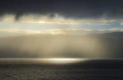 Sonnenlicht durch Regen durch den Fjord Lizenzfreie Stockbilder
