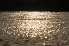 Sonnenlicht von den Sonnenuntergängen nachgedacht über das Wasser stockbild