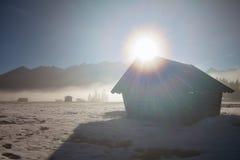 Sonnenschein über hölzerner Hütte in den Alpen Stockfotos