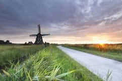 Sonnenschein über Landschaftsstraße und -windmühle stockfotos