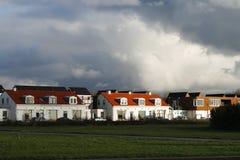 Sonnenschein auf Häusern unter einem Donnerhimmel Stockfoto