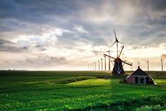 Sonnenschein hinter alter Windmühle und modernen Mühlen stockfotografie