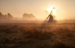 Sonnenschein hinter Windmühle im Morgennebel Stockfotos