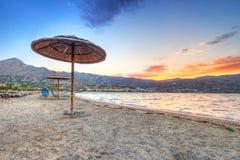Sonnenschirm an Mirabello Bucht am Sonnenuntergang Lizenzfreie Stockbilder