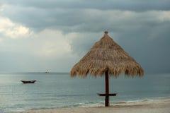 Sonnenschirm und ein Fischerboot stockfotos