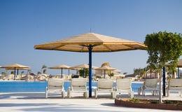 Sonnenschirm und Liege im Hotel Lizenzfreie Stockfotos