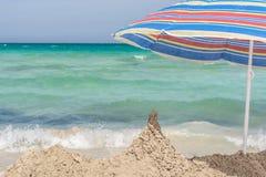 Sonnenschirm und Sandburg auf dem schönen Strand stockfoto
