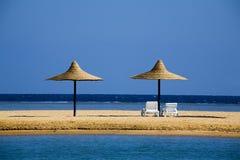 Sonnenschirme auf einem Strand morgens Stockfotos