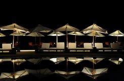 Sonnenschirme durch das Pool nachts Lizenzfreie Stockfotos